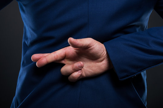 Closeup view of businessman standing with crossed fingers