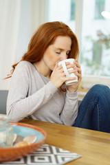 frau trinkt eine tasse tee in ihrer wohnung
