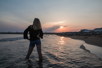 Blond teenager girl on the beach during sunset