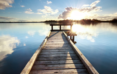 gold sunshine over wooden pier on big lake