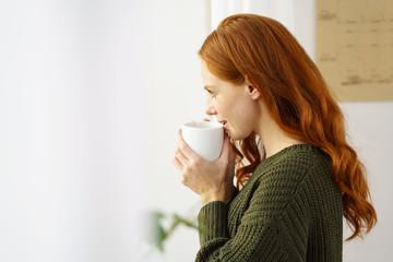 frau schaut aus dem fenster und genießt eine tasse tee