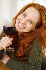 lächelnde frau hält ein glas rotwein in der hand