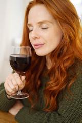 frau genießt ein glas rotwein mit geschlossenen augen