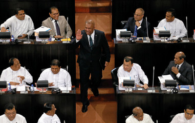 Sri Lanka's Finance Minister Mangala Samaraweera gestures as he arrives at parliament to present the 2018 budget proposals in Colombo