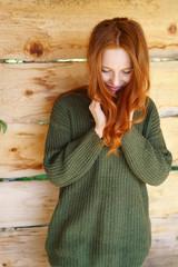 lächelnde frau mit langen roten haaren steht draußen
