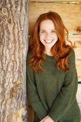 glückliche frau mit langen roten haaren lehnt an einem baumstamm