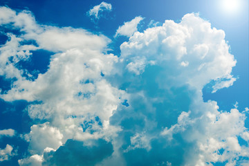 Bright blue sky with curly clouds background