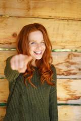 lachende frau steht draußen und zeigt mit dem finger nach vorne