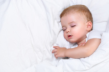 Cute one year old baby boy sleeping in a white bed