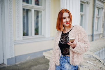 Red haired girl with red handbag posed near vintage house and speaking on mobile phone.