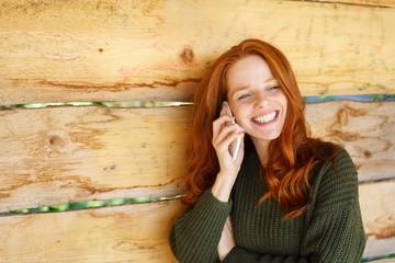 frau steht lächelnd draußen an einer holzwand und telefoniert