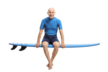 Elderly surfer sitting on a surfboard and smiling
