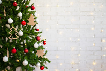 christmas tree over white brick wall with lights
