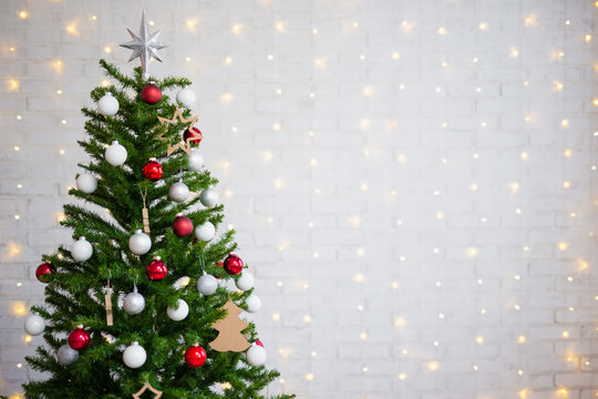 decorated christmas tree over white brick wall with lights