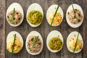 Variety of stuffed eggs with avocado and tuna on wooden table.Top view