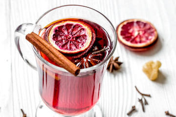 mulled wine with spices in cup on wooden background