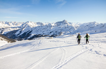 Two snowshoe hikers in alpine winter mountains. Bavaria, Germany.