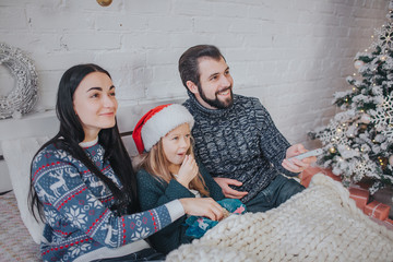Merry Christmas and Happy New Year!. Young family celebrating holiday at home. The Father is holding the remote from the TV. Dad, daughter and mother are watching television