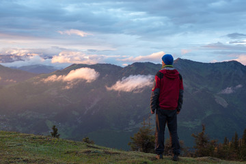 Traveler in the mountains admires sunset after storm