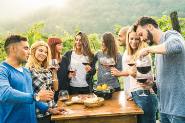 Group of happy friends having fun outdoors drinking red wine - Young people eating local fresh food at grape harvesting in farmhouse vineyard winery - Youth friendship concept on a vivid warm filter