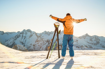 Young professional skier at sunset on relax moment in french alps ski resort - Winter sport concept with adventure guy on mountain top ready to ride down - Backlight view point with bright warm filter