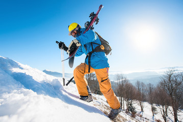 Male skier walking up the snowy hill in the mountains carrying his equipment copyspace active lifestyle sportsman seasonal recreation resort activity. Blue sky and winter forest on the background