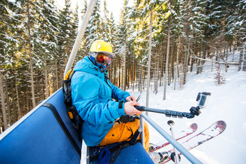 Male skier taking selfies with action camera on selfie stick while riding up on ski lift in the mountains at the winter resort