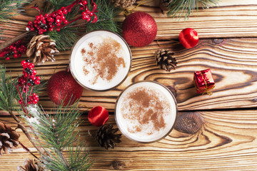 Glass of eggnog on wooden background