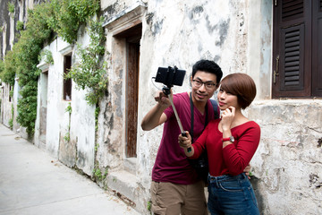Asian couple traveler taking selfie photo with selfie stick with vintage town in background.
