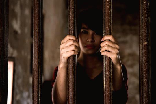 beautiful teenager girl behind the wooden bar, prisoner concept.