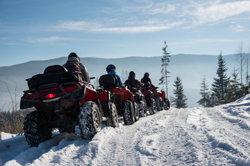 Group of people driving four-wheelers ATV bikes on snow at top of the mountain in winter