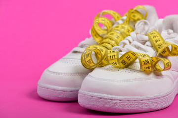 Sneakers with measuring tape on pink background.