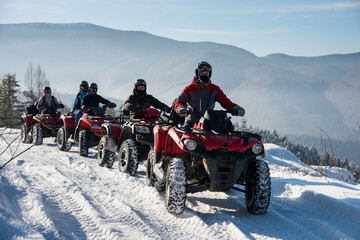 Four ATV riders on off-road four-wheelers ATV bikes on snow in the winter mountains