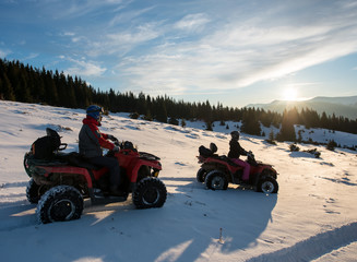 Man and woman sitting on four-wheelers ATV bikes on snow, enjoying sunset in the the mountains in winter