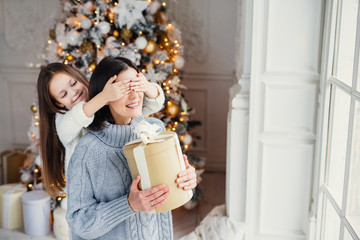 Portrait of little girl closes mother`s eyes, congratulates her with New Year or Christmas, stand near window in living room, have real miracle and feeling of holiday. Winter, celebration, season