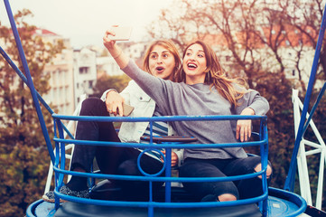 Two girls taking selfie while having fun in amusement park