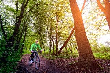 Young man riding a mountain bike through the woods.