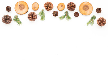 Christmas wood slice decorations, pine cone, spruce branches on white background, flat lay, top view, copy space