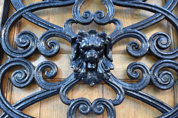 Décor en fer forgé à tête de lion sur porte en bois