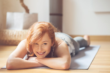 Smiling woman on yoga mat