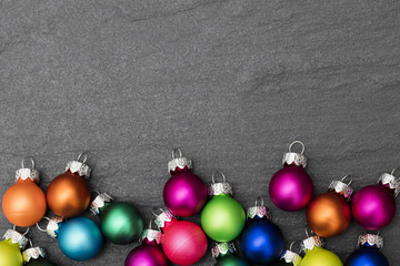 Festive Christmas baubles on a slate background