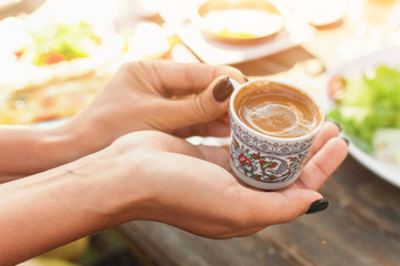woman's hand holding a cup of traditional Turkish coffee at outdoor cafe