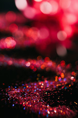 Multicolor glitter on black contrast background. Defocused bokeh blur flares concept