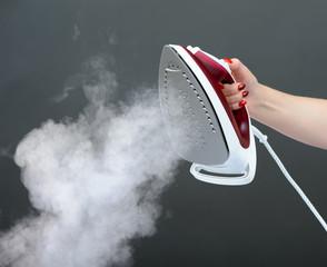 Iron with steam on dark grey background