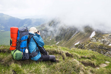 Mountain photographer and hiker with backpack and equipment outdoor on mountain peak