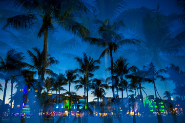 Multiple exposure view at dusk of palm trees and neon lights of Ocean Drive in South Beach, Miami, Florida.
