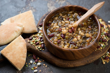 Wooden bowl with thick mexican bean soup and pita bread, studio shot