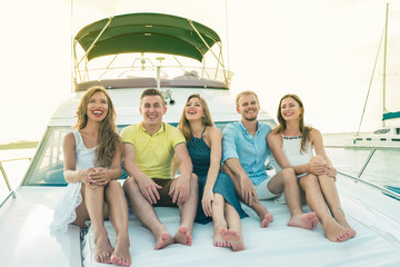 Group of happy people sitting on the deck of yacht. Sunset, luxury yacht. Selective focus.