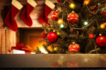 A wooden table with space for your advertisement. Great green Christmas tree. Fireplace with flames. Red socks of Santa Claus.