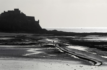 A man walks out on the tidal causeway to Elizabeth Castle in St Helier